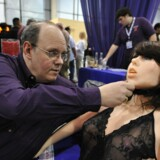 "Opfinderen af Roxxxy Douglas Hines præsenterede sexrobotten i 2010, adjusts the head of his company's ""True Companion"" sex robot, Roxxxy, at the TrueCompanion.com booth at the AVN Adult Entertainment Expo in Las Vegas, Nevada, January 9, 2010. In what is billed as a world first, a life-size robotic girlfriend complete with artificial intelligence and flesh-like synthetic skin was introduced to adoring fans at the AVN Adult Entertainment Expo. AFP PHOTO / Robyn Beck"