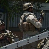 """Afghan security forces keep watch at the site of a suicide blast near Iraq's embassy in Kabul on July 31, 2017. A series of explosions and the sound of gunfire shook the Afghan capital on July 31, with a security source telling AFP that a suicide bomber had blown himself up in front of the Iraqi embassy. """"Civilians are being evacuated"""" from the area as the attack is ongoing, said the official, who declined to be named. / AFP PHOTO / SHAH MARAI"""