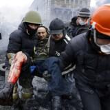 Demonstranter bører en såret mand væk i Kiev.