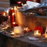 En kvinde tænder et lys ved rådhuset i Saint-Etienne-du-Rouvray i Frankrig, for at mindres præsten, der blev dræbt i endnu et terrorangreb i Frankrig tirsdag.