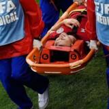 William Kvist måtte bæres fra banen efter at være blevet ramt af et knæ i brystkassen. / AFP PHOTO / JUAN BARRETO