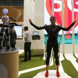 An SK telecom exhibitor directs the robot's movements using 5G on the last day at the Mobile World Congress in Barcelona March 5, 2015