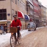 Vinteren 1969: I regn og slud skal cykelposten ud. Et af de klassiske røde postbude stamper sig gennem snesjappet i København. Foto: Steen Jacobsen