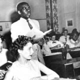 d. 21 maj, 1954. En sort studerende, Nathanial Steward, læser op fra en bog i et klasse lokale med både hvide og sorte elever. Billedet er taget på the Saint-Dominique School i Washington, der som en af de første skoler afskaffede raceadskillelse i klasselokaler.