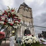 Folk har lagt blomster ved Saint Etienne-kirken, hvor en præst blev dræbt.
