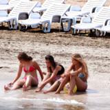 Badeferie ved Sortehavet i Rumænien. Tre piger i sandet med tæerne i vandet