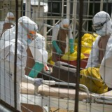 British health workers lift a newly admitted Ebola patient onto a wheeled stretcher in to the Kerry town Ebola treatment centre outside Freetown December 22, 2014. REUTERS/Baz Ratner (SIERRA LEONE - Tags: HEALTH POLITICS)