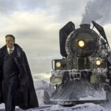 Poirot i Kenneth Branaghs skikkelse foran Orient Ekspressen i filmen, hvor der sker et mord i toget.