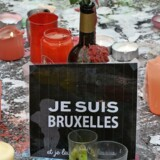 A sign reading »I am Brussels« (Je suis Bruxelles) is placed between candles and flowers at a makeshift memorial at Place de la Bourse (Beursplein) in Brussels on March 23, 2016. World leaders united in condemning the carnage in Brussels and vowed to combat terrorism, after Islamic State bombers killed around 35 people in a strike at the symbolic heart of the EU. / AFP PHOTO / PATRIK STOLLARZ