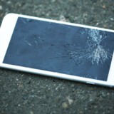 Broken iPhone on asphalt outdoors