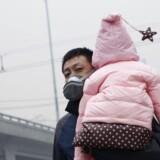 8. december 2015. En far forsøger at beskytte sig og sin baby mod den ekstraordinære luftforurening i Beijing. Foto: Kim Kyung-Hoon