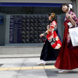 "Women wearing Hakama, or Japanese traditional Kimono, walk past an electronic board, showing the various stock prices, outside a brokerage in Tokyo, in this March 23, 2015 file photo. Japan is expected to announce consumer confidence data for April this week. REUTERS/Yuya Shino/Files GLOBAL BUSINESS WEEK AHEAD PACKAGE - SEARCH ""BUSINESS WEEK AHEAD MAY 11"" FOR ALL IMAGES"