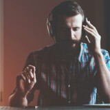 handsome bearded man in headphones listening to music with laptop