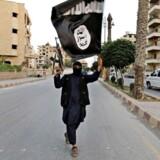 Arkivfoto. Et medlem af Islamisk Stat holder terrorbevægelsens ikoniske sorte flag i Raqqa, juni 2014. Siden 2012 har mindst 125 danskere tilsluttet sig organisationen, og én af dem - en hjemvendt 23-årig mand - er nu tiltalt efter terrorparagrafferne for denne tilknytning. Foto: Reuters/Stringer/Syrien