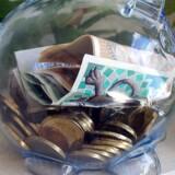 Pengesedler og mønter i plastic sparegris.