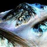 De mørke, smalle og flere hundrede meter lange streger på Mars er formentligt blevet skabt af flydende saltvand, som løber ned ad kløfter og kratervægge. Foto: NASA