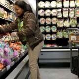 Walmart-medarbejder Inirida Olivares fylder hylderne hos verdens største detailkæde, Walmart, i en butik i Miami, Florida. Kæden vil fra og med næste år vil hæve mindstelønnen for sine ansatte i USA til ti dollar i timen.