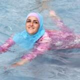 En ung, tyrkisk kvinde bader i burkini i et friluftsbad i Berlin.