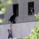 En dreng evakueres fra det iranske parlament efter bygningen kom under angreb. Islamisk Stat har taget ansvar for angrebene i Teheran, der mindst har kostet 12 mennesker livet 7. Juni, 2017. Omid Vahabzadeh/TIMA via REUTERS