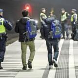 En svensk politibetjent eskorterer illegale migranter fra toget ved stationen i Hyllie uden for Malmø i november 2016. Foto: Johan Nilsson