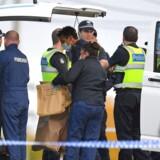 Australske efterforskere i færd med at indsamle bevismateriale. På billedet holder en efterforsker en brun papirpose, hvorpå der står »hardback bog med arabisk skrift«.