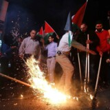 Palæstinensere står med flag og bannere, hvor der står »vi kommer tilbage«, i byen Hebron 13. maj forud for USAs indvielse af en ambassade i Jerusalem.