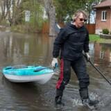 En mand trækker en kano efter sig i det oversvømmede område Pirrefonds i Montreal, Canada søndag 7. maj 2017.