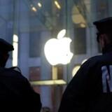 To betjente fra politiet i New York på vagt ved Apple-butikken på Fifth Avenue, hvor der tirsdag var demonstration mod regeringen i sagen, hvor Apple afviser at ville bistå forbundspolitiet FBI med at hacke sig ind i en krypteret mobiltelefon, som attentatmanden bag massakren i San Bernardino i december havde på sig, da han selv blev dræbt. Foto: Jewel Samad, AFP/Scanpix