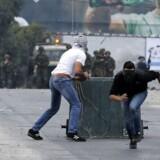 Palæstinensiske demonstranter løber i dækning under kampene med israelske styrker efter Donald Trumps udtalelser om at ville erklære Jerusalem som Israels hovedstad.