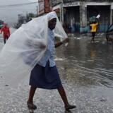 En kvinde i Haitis hovedstad Port-au-Prince beskytter sig mod den piskende regn, endnu før orkanen for alvor er over den fattige nation.