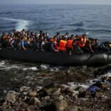 En afghansk flygtning hopper ud af en overfyldt båd på en strand på den græske ø Lesbos i oktober 2015. Reuters/Yannis Behrakis