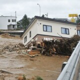 Et hus er blevet revet med af strømmen i en flod i byen Shimizu i Hokkaido i forbindelse med, at en tyfon har hærget området.