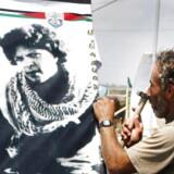 BMINTERN - Her ses en libanesisk mand hænge en plakat med Dalal al-Mughrabi i det sydlige Libanon i 2008. For mange palæstinensere er al-Mughrabi indbegrebet af en frihedskæmper, mens hun af andre opfattes som en ærketerrorist. Hun tog del i et angreb i 1978, der dræbte 38 israelere. Nu skærper Danmark kravene for bistand til palæstinensiske organisationer, som resultat af den undersøgelse udenrigsminister anders Samuelsen satte i gang efter en palæstinensisk organisations rolle i åbningen af Dalal al-Mughrabi centeret i byen Burqa. AFP PHOTO/RAMZI HAIDAR. RAMZI HAIDAR / AFP