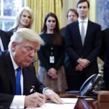 Præsident Donald Trump omgivet af et udsnit af sine medarbejdere i Det Hvide Hus, mens han underskriver et præsidentielt dekret tirsdag.
