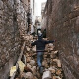 En syirsk dreng på vej gennem ruinerne af en ødelagt bygning i Dahret Awad i Aleppo