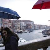 Turister bruger mobilen på ferie i den populære italienske ferieby Venedig. Netop brug af mobil- og dataabonnementer på ferier skal fra sommeren 2017 være uden merpris ifølge et prestigeforslag fra EU. Men de store ferielande i Sydeuropa kæmpe for at beholde høje datapriser. / AFP PHOTO / MARCO BERTORELLO