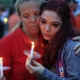 Naboer og bekendte i mindehøjtidelighed for de otte drabsofre i Ohio. Amber Cassell, 16 år, omfavnes af Margaret Williams (tv.). Foto: Kyle Robertson