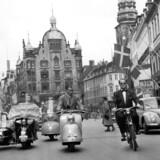 I 1954 var der masser af trafik på Strøget, for dengang var strækningen endnu ikke en gågade. Det skete først den 17. november i 1962, hvor ca. 25.000 mennesker med byplanborgmester Alfred Wassard i spidsen indviede den nye bilfrie gågade med et langt optog. Kilde: Københavns Stadsarkiv