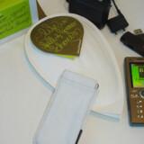 Det bladformede, hvide papirhylster i midten er fremtidens æske. Heri kan mobiltelefonen ligge i det ligeledes hvide polyesterfutteral (forrest), som beskytter den. Batteriet sidder i telefonen for at spare plads. Det er slut med brugsanvisninger på papir; e-manualen, som ses på mobiltelefonen, ligger på den medfølgende USB-pind (oven for telefonen). Endelig er strømforsyningen dels fremstillet i materialer, som kan genbruges, dels ændret, så den bruger 99 procent mindre strøm, når den sidder ubrugt i stikkontakterne. Sony Ericsson overvejer, om strømforsyningen skal kunne købes separat (i æsken øverst til venstre), fordi mange holder ved deres gamle telefonmærke og derfor allerede har en strømforsyning.