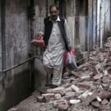En mand går med sine få ejendele forbi resterne af et hus i Mingora, der ligger i Swat-dalen i Pakistan.