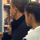 Barack Obama læser beskeder på sin Blackberry-telefon i selskab med døtrene Sasha (til venstre) og Malia. Arkivfoto: Saul Loeb, AFP/Scanpix