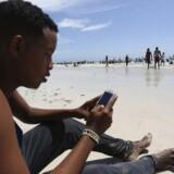 En somalier går på Internet fra sin mobiltelefon på stranden langs Det Indiske Ocean ved hovedstaden Mogadishu. Arkivfoto: Feisal Omar, Reuters/Scanpix