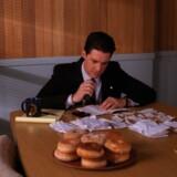 FBI-agent Dale Cooper spillet af Kyle MacLachan. På bordet et fad donuts – en mærkelig kage som ingen kendte til i Danmark, da »Twin Peaks« rullede hen over TV-skærmene. Foto: PR