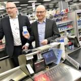 Kenneth Nielsen, digitalchef i Dansk Supermarked og Jesper Nielsen, direktør i Danske Bank(tv) har samarbejdet om, at kunder i supermarkedskæderne Føtex, Bilka, Salling og Netto fremover vil kunne bruge deres mobiltelefon og Mobilepay-appen til at betale med. Ved kassen sidder kassedame Michelle Mogensen.