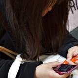 Ung pige på gaden i Tokyo har gang i to mobiltelefoner.