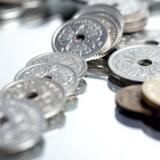 Danske mønter på et spejl med hvid baggrund.