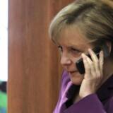 Også forbundskansler Angela Merkel betaler højere priser, når hun bruger mobiltelefonen i udlandet. Og det skal være slut, mener EU, som dog samtidig vil indføre et års binding til teleselskabet i hele Europa. I Danmark må privatkunder højst bindes i seks måneder. Arkivfoto: Yves Herman, Reuters/Scanpix