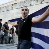 En anti-EU-demonstrant folder det græske flag ud foran uropoliti på trappen op til den græske parlamentsbygning i Athen.