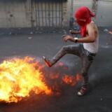 En unge palæstinenser sparker til et brændene dæk under sammenstød med israelske sikkerhedsstyrker på Vestbredden søndag 4. oktober.