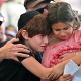 Mindst 97 palæstinensere og 13 israelske soldater blev dræbt i går, da Israel optrappede den militære offensiv til det, der skulle blive den blodigste enkeltdag i Gaza i fem år. Her er det børnene Ori og Shirai, der sørger over tabet af deres far, Amotz Greenberg, en 45-årig israelsk reservesoldat, der var blandt de dræbte i kampene med Hamas og militante palæstinensere.